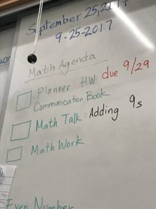 "below eye level picture looking up on white board at date written two ways in blue white board marker ""September 25, 2017, 9-25-2017"" Under, ""Math Agenda"" with an underline in faded black marker Green marker with large square bullet points ""Planner HW due 9/29, Communication book"" date written in red white board marker, ""Math talk 'Adding 9's"" 'adding 9's written in black', ""Math Work""."