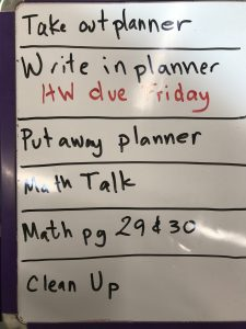 "small white board with purple edges, metal corners. Visual schedule written in black for separated with solid black line between tasks. ""Take out planner"", ""Write in planner"" in red: ""HW due Friday"", ""Put away planner"", ""Math Talk"", ""Math page 29 & 30"", ""Clean Up"""